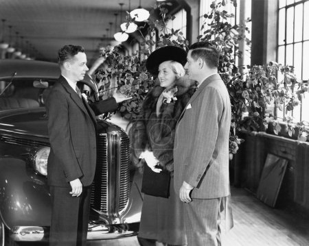 Photo for Man and woman standing in a car showroom talking to a salesman - Royalty Free Image