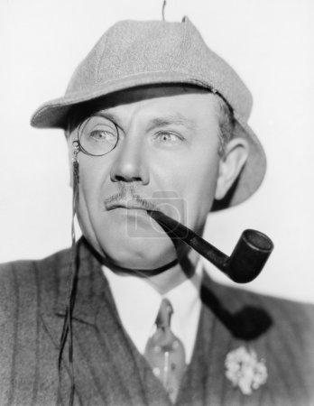 Homme avec un monocle, une pipe et un chapeau de chasseur de cerfs