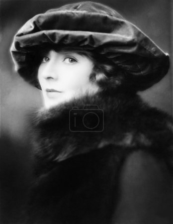 Portrait of a young woman wearing a hat and a fur stole