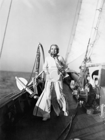 Young woman standing on a deck of a sailboat and smiling