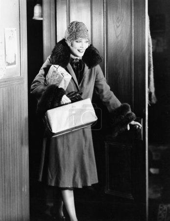 junge Frau in Mantel und Hut betritt ein Zimmer