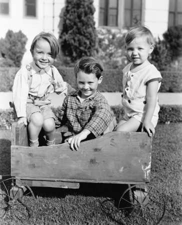 Three boys sitting in a push cart and smiling