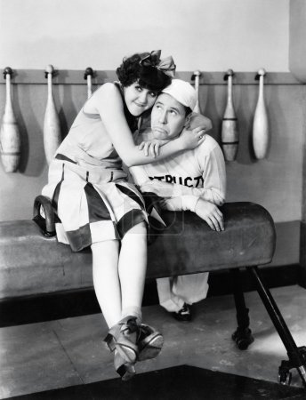 Young woman embracing a young man on a pommel horse