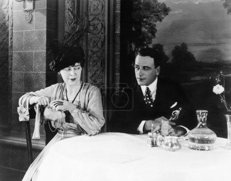 Paar sitzt an einem Tisch in einem Restaurant und schaut sich an