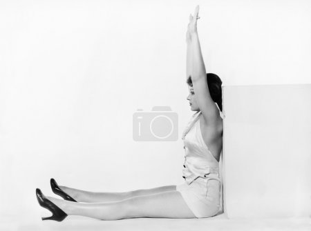 Photo for Profile of a young woman exercising against a cube - Royalty Free Image
