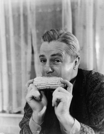 Porträt eines Mannes, der einen Maiskolben isst
