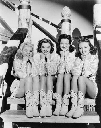 Photo pour Portrait de quatre jeunes femmes assises sur des marches en vêtements occidentaux - image libre de droit