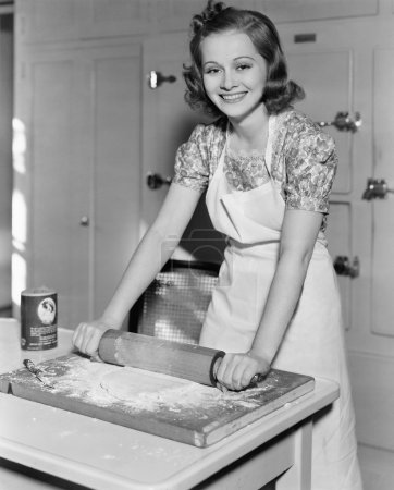 Photo for Young woman rolling out dough in the kitchen - Royalty Free Image
