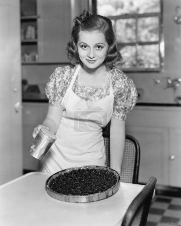 Portrait of a young woman preparing a blueberry pie in the kitchen