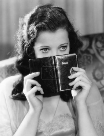 Portrait of a young woman holding a diary and thinking