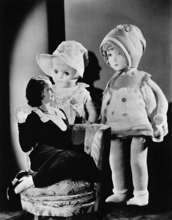 Woman sitting on a chair and looking at two oversized dolls