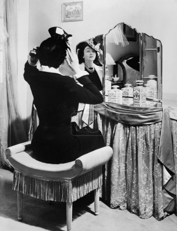 Woman putting on a hat in front of a dressing table