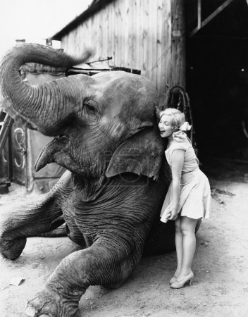 Profile of a young woman hugging an elephant