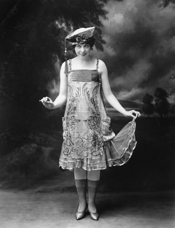 Woman wearing a hat and ornate dress and smiling