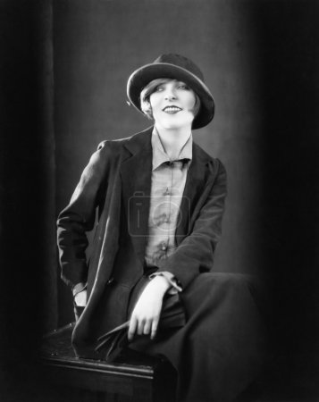 Portrait of a woman sitting on a stool and smiling