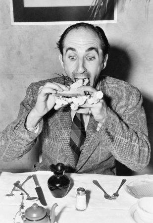 Mann sitzt am Esstisch und versucht, ein Sandwich zu essen