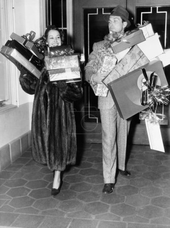 Couple walking and holding stacks of presents
