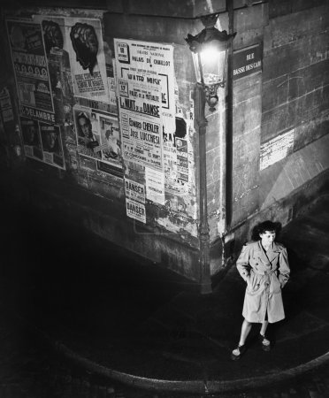 High angle view of a young woman waiting next to a lantern on a dark street corner
