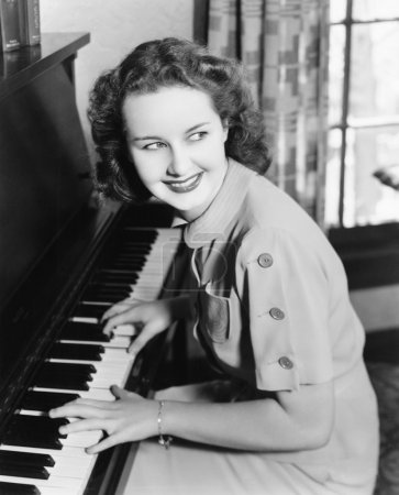 Profile of a young woman playing a piano and smiling