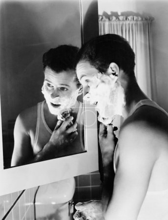 Profile of a young man in front of a mirror in a bathroom shaving