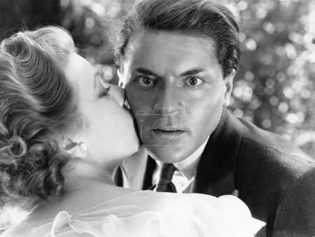 Close-up of a young man being kissed by a young woman and looking surprised
