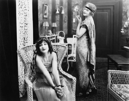 Frau sitzt im Sessel, im Hintergrund raucht eine andere Frau eine Zigarette