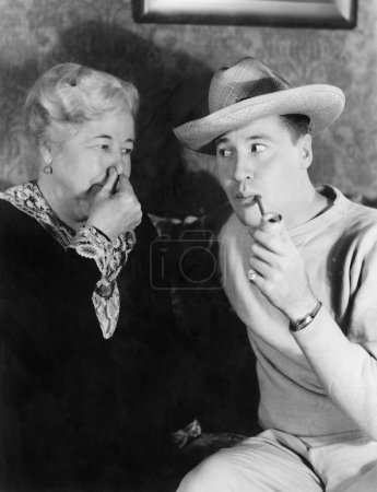 Young man smoking a pipe with a woman holding her nose