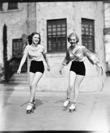 Two young women roller skating on the road and smiling