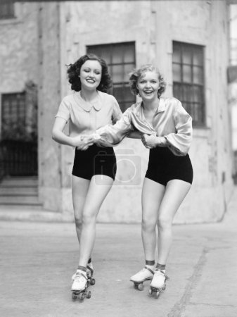 Photo for Portrait of two young women with roller blades skating on the road and smiling - Royalty Free Image