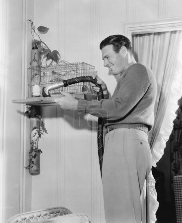 Profile of a man cleaning a cage with a vacuum cleaner
