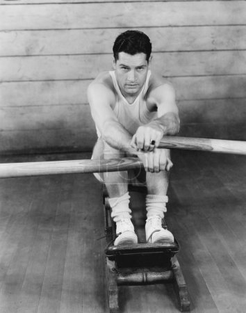 Portrait of a young man exercising on a rowing machine