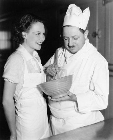 Profile of a chef stirring a mixture in a bowl and a young woman standing beside him