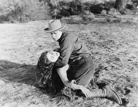 Young man holding an unconscious young woman
