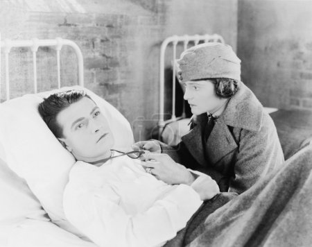 Young woman looking at a locked of a young man who is lying on the bed in a hospital