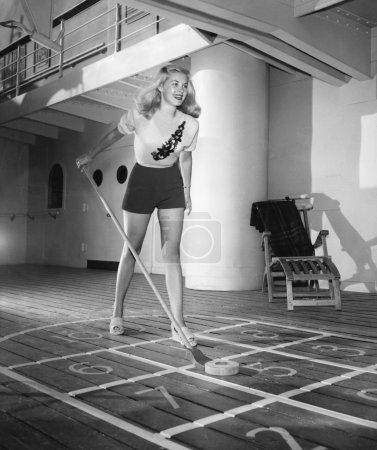Young woman playing shuffleboard