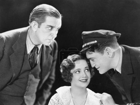 Photo pour Jeune homme qui chuchote à une jeune femme et un autre jeune homme, debout à côté d'eux à l'écoute pour eux - image libre de droit