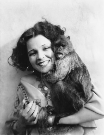 Portrait of a young woman hugging her monkey