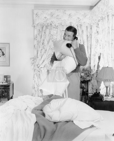 Young man talking on the telephone and biting into a pillows