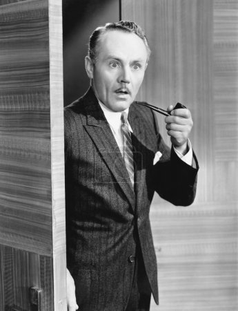 Man holding a pipe and standing at a doorway looking very surprised