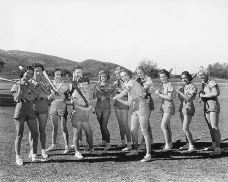 Group of women holding baseball bats and standing in a row