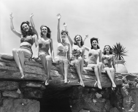 Low angle view of a group of women sitting on a stone structure and waving their hands
