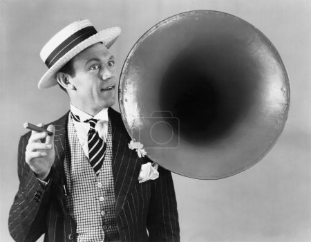 Man holding a cigar and standing near a victrola horn