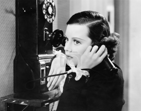 Profile of a young woman talking on a payphone