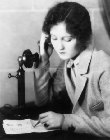 Close-up of a woman talking on the telephone and drawing on a sheet of paper