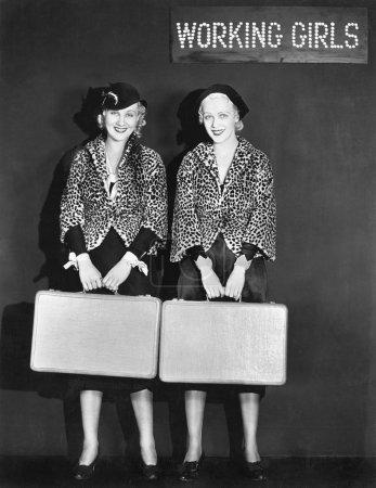 portret dwóch stewardesa gospodarstwa walizki i uśmiechając się