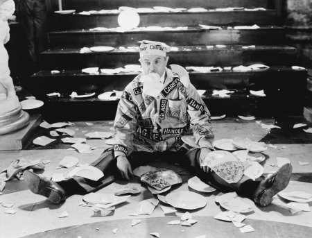 Man sitting in front of a staircase with broken plates around him