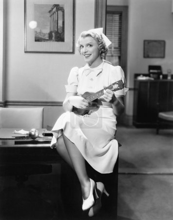 Portrait of a female nurse sitting on a table and playing a guitar