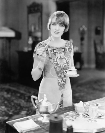 Woman with a cup of tea and a canapé in her hands