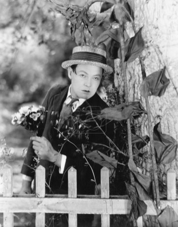 Young man hiding behind a tree with a bouquet of flowers in his hands