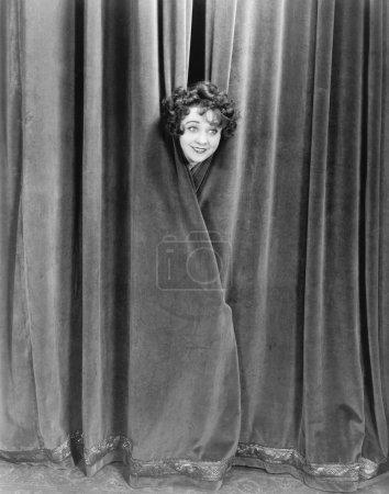 Woman peek-a-booing behind a curtain
